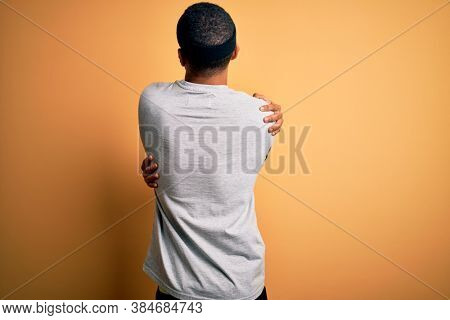 Handsome african american sportsman doing sport wearing sportswear over yellow background Hugging oneself happy and positive from backwards. Self love and self care