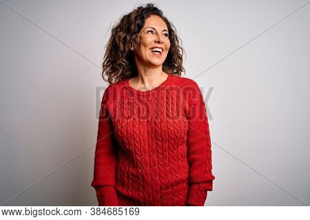 Middle age brunette woman wearing casual sweater standing over isolated white background looking away to side with smile on face, natural expression. Laughing confident.