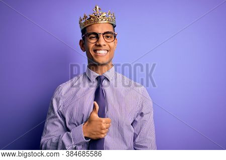 Young handsome african american man wearing golden crown of king over purple background doing happy thumbs up gesture with hand. Approving expression looking at the camera showing success.