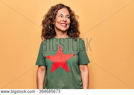 Middle age beautiful woman wearing t-shirt with red star revolutionary symbol of communism looking to side, relax profile pose with natural face and confident smile.