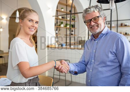 Happy Business Partners Of Different Ages Meeting And Shaking Hands. Mature Man And Young Woman In C