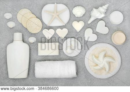 Natural organic beauty treatment products for skin care with soaps, moisturising cream, cleansing sponges and scrubs. Flat lay on mottled grey background.