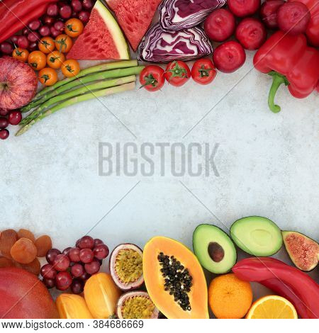 Healthy food border high in lycopene with fruit & vegetables for immune defence also high in antioxidants, anthocyanins, vitamins, minerals, vitamins & dietary fibre. Foods for heart health concept.