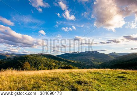 Rural Landscape In Mountains At Sunset. Grassy Pasture On The Hill In Evening Light. High Mountains