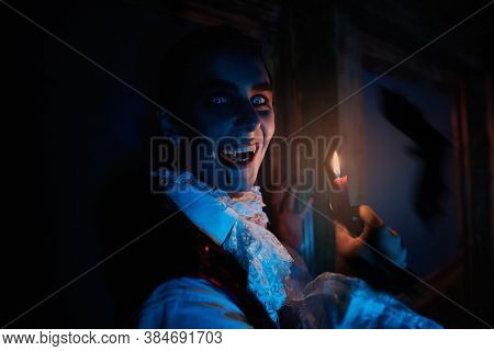 Portrait of bloodthirsty laughing vampire aristocrat in the candlelight in a night castle. The style of the 19th century. Halloween.