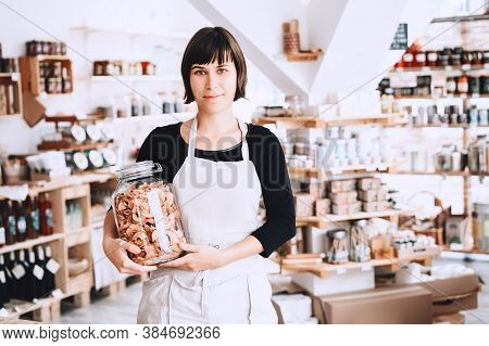 Caucasian Woman In Zero Waste Shop. Cheerful Seller Assistant Holding Glass Jar With Groceries In Pl