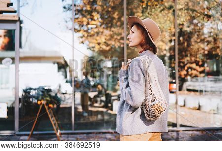 Stylish Woman With Purchase In Cotton Reusable Net Bag And Glass Cup On Storefront Background Of Zer