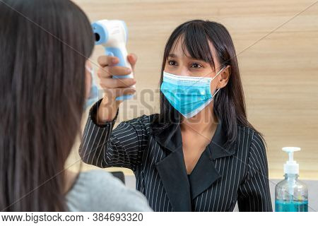Receptionist And Guest Wearing Face Mask At Front Desk While Having Conversation In Office Or Hospit