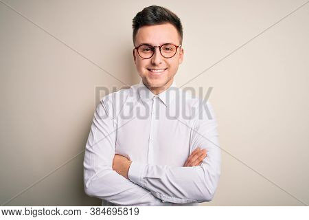 Young handsome business mas wearing glasses and elegant shirt over isolated background happy face smiling with crossed arms looking at the camera. Positive person.