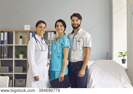 Group Portrait Of Three Smiling Young Healthcare Providers In Modern Clinic Office