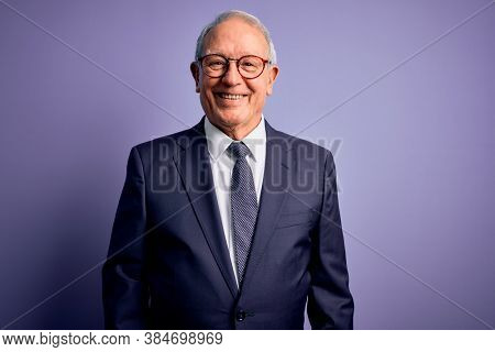Grey haired senior business man wearing glasses and elegant suit and tie over purple background with a happy and cool smile on face. Lucky person.