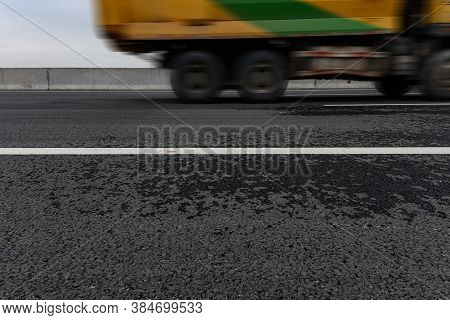 White Divider Line On Blacktop With A Truck Passing
