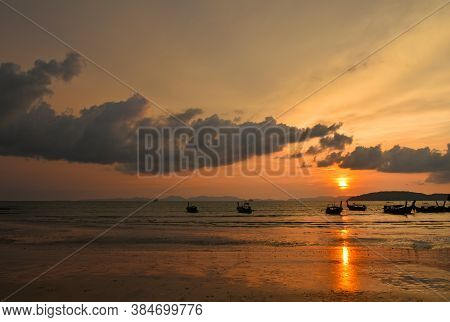 Scenic Late Sunset Sea Landscape With Traditional Thai Longtail Boats And Dramatic Cloudy Sky