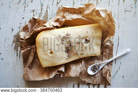 Maasdam Cheese Sprinkled With Lavender On Craft Paper And Old Light Background With Cracked Paint
