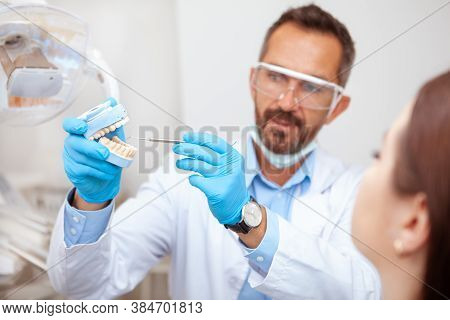 Experienced Mature Male Dentist Explaining Dental Hygiene To His Female Patient, Holding Teeth Mold