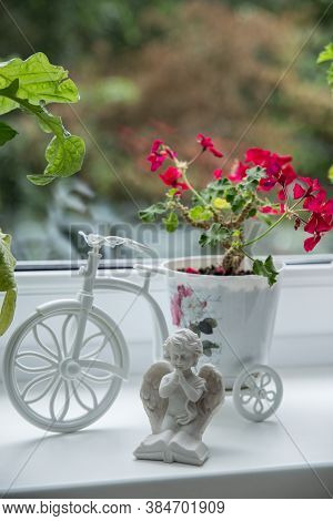 Red Geranium Flowers In Pots On The Windowsill, Next To A Statuette Of An Angel. Beautiful Little Ge