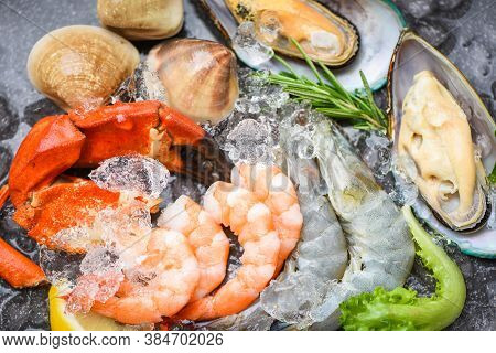 Fresh Raw Seafood Buffet With Lemon Rosemary Ingredients Herb And Spices / Seafood Shellfish On Ice