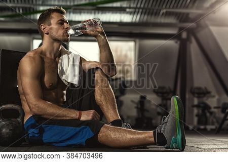 Drink Water. Shirtless Sportsman Resting After Training At The Gym Sitting On The Floor Drinking Wat