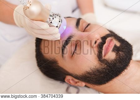 Close Up Of A Male Client Enjoying Anti-aging Facial Rf-lifting Treatment By Cosmetician