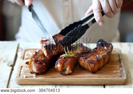 Appetizing Bbq Ribs. Chef With A Knife Cuts Barbecue Ribs On The Board.
