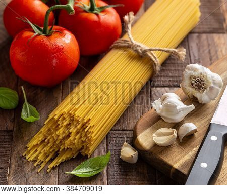 Raw Spaghetti Pasta Tied In A Bundle With Fresh Vine Tomatoes, Garlic And Basil On A Rustic Wooden T
