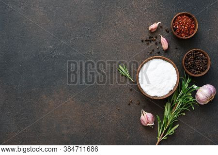 Peppercorns, Garlic And Fresh Rosemary On A Concrete Background.