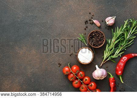 Spices, Chili Peppers And Tomatoes On A Dark Concrete Background. View From Above.