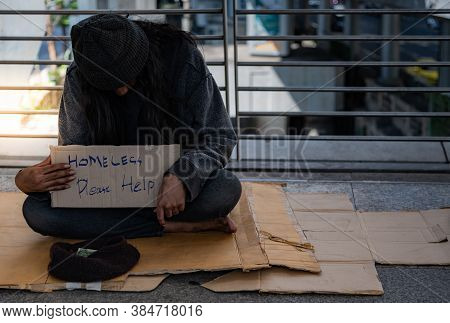 Beggars, Homeless People Sitting On The Floor On An Overpass, Asking For Money From People Traveling