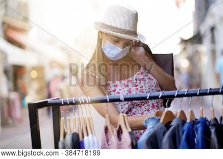 Young woman doing shopping in tourist area, wearing face mask