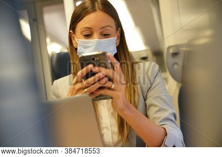 Businesswoman commuting by train, connected on smartphone and wearing face mask