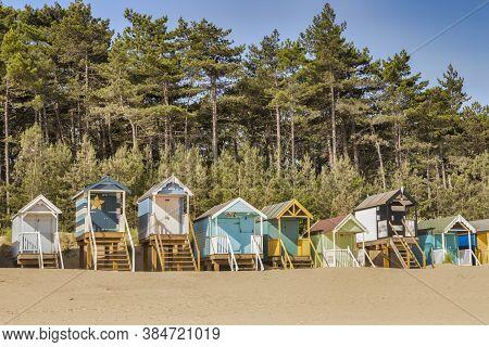 29 June 2019: Wells-next-the-sea, Norfolk, England, Uk - Bathing Huts On The Beach, Pine Trees Behin