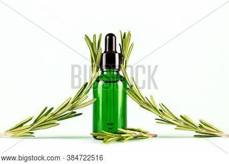 Rosemary Essential Oil. Dropper Bottle With Natural Cosmetic Oil And Fresh Rosemary On A Light Backg