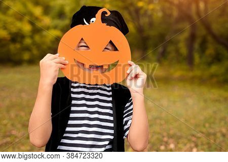 Little Boy In Carnival Costume Of Pirate Holding Paper Pumpkin Mask And Looking At Camera On Blurred