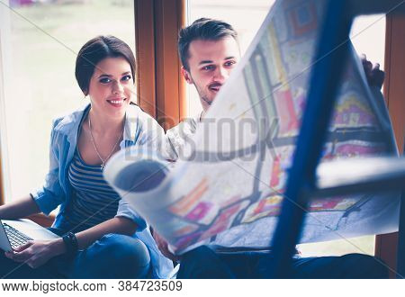 Young Couple Sitting On The Floor And Looking At The Blueprint Of New Home