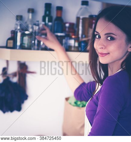 A Young Woman Choosing In Her Kitchen .