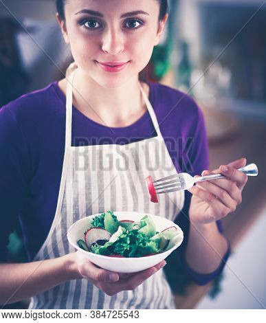 A Young Woman Eating Salad In Her Kitchen .
