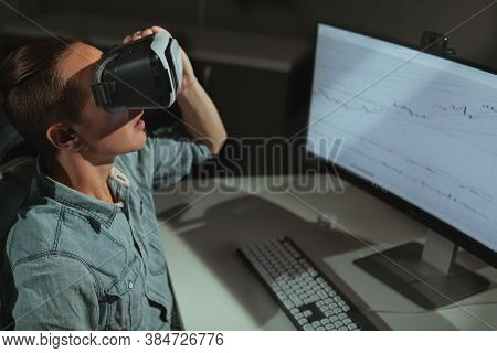 Young Man Using Virtual Reality Goggles, Sitting In Front Of His Compputer Late At Night. Male Freel