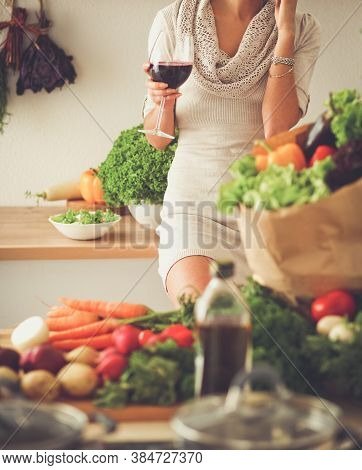 Young Woman Cutting Vegetables In Kitchen, Holding A Glass Of Wine