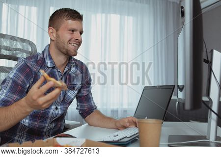 Happy Handsome Man Studying Online, Eating Pizza In Front Of His Computer. Cheerful Male Program Dev