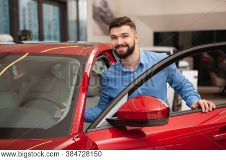 Happy Young Handsome Man Getting Into The Car At The Dealership Salon. Attractive Male Driver Trying