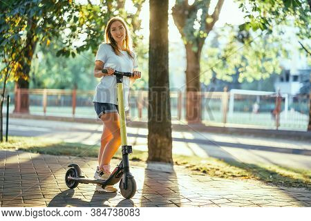 Smiling Woman Rides Electric Scooter Or E-scooter In City Park At Sunset. Female Using Electric Tran