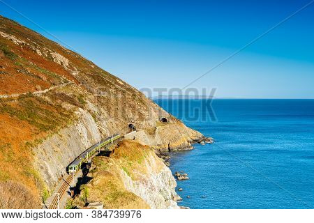 Train Exiting A Tunnel. View From Cliff Walk Bray To Greystones With Beautiful Coastline, Cliffs And