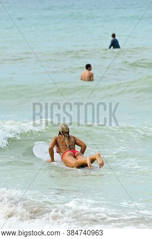 Young Woman Surfing With Friends
