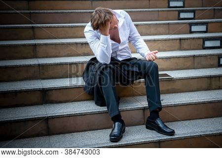 Caucasian Businessmen Sitting On Concrete Stairs, Being Stressed And Tired Because Of Business Probl