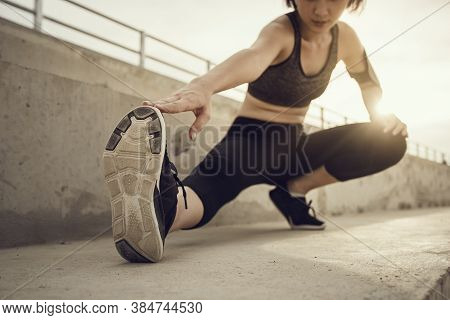Focus Shoe And Hand, Runner Doing Stretching Exercises On Stair Before Running At Sunset. Asian Woma
