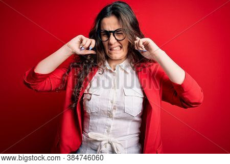 Young beautiful woman with curly hair wearing jacket and glasses over red background covering ears with fingers with annoyed expression for the noise of loud music. Deaf concept.