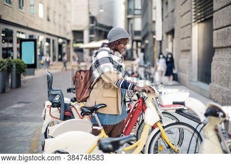 woman takes a public bike in the street