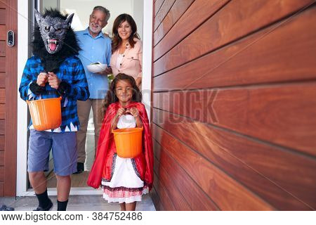Two Children Wearing Fancy Dress Outside House Collecting Candy For Trick Or Treat From Grandparents