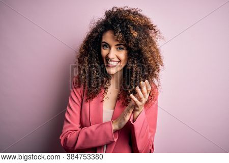Young beautiful businesswoman with curly hair and piercing wearing elegant jacket clapping and applauding happy and joyful, smiling proud hands together