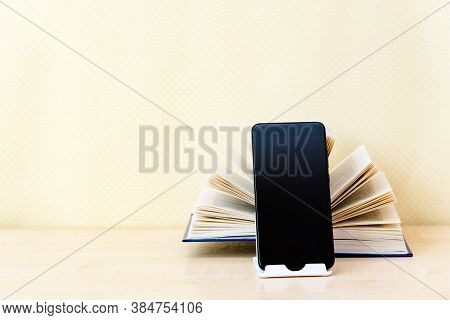 Open Old Paper Book Back In The Foreground Modern Digital Gadgets: Tablet, Phone. Concept New Techno